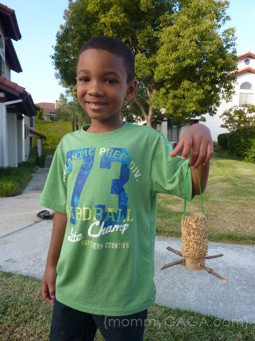 Kid holding his DIY bird feeder craft