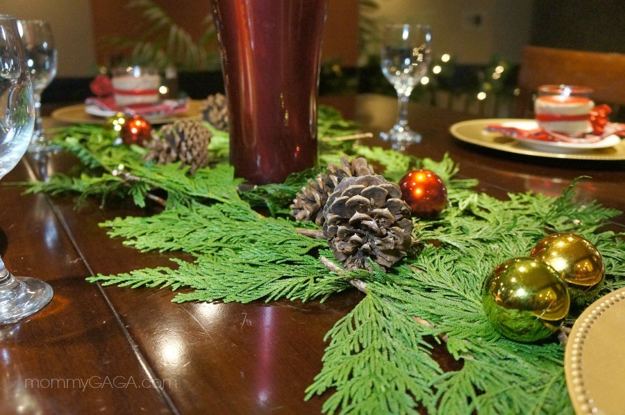Decorate your Christmas dinner table with fresh greenery and pine cones