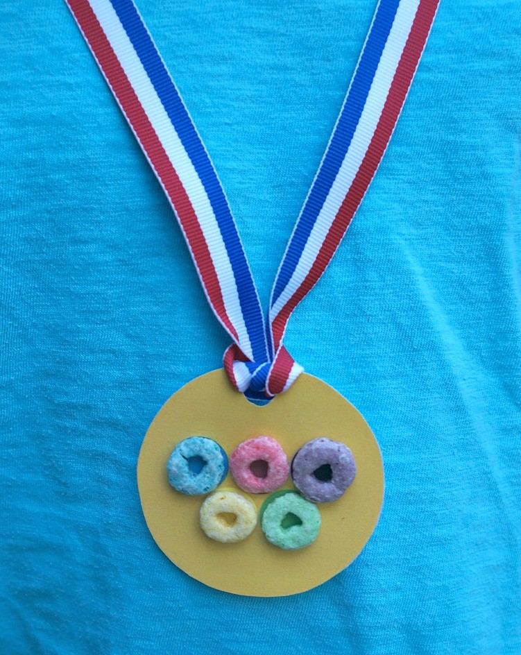 Gold medal Olympic rings craft made with Fruit Loops - the kids can compete in their own Olympic games and wear these medals as they cheer on team USA!