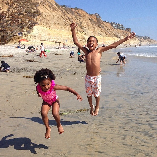 kids jumping at the beach