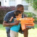 Father and son play with Nerf dart blaster