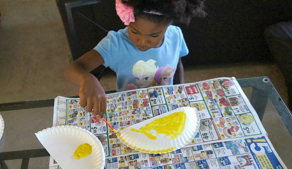 Girl painting paper plate for school bus shapes craft