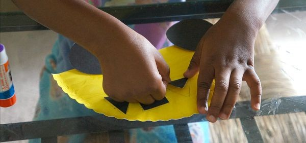 Glue shapes onto your paper plate school bus