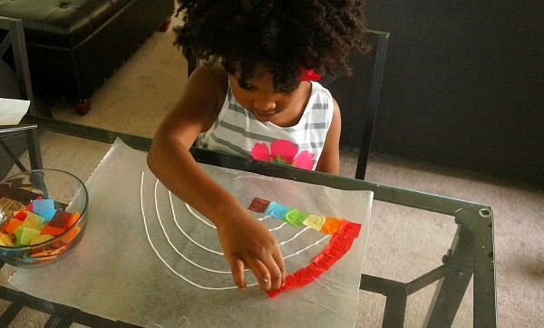 How to make a rainbow suncatcher craft, little girl glues tissue squares