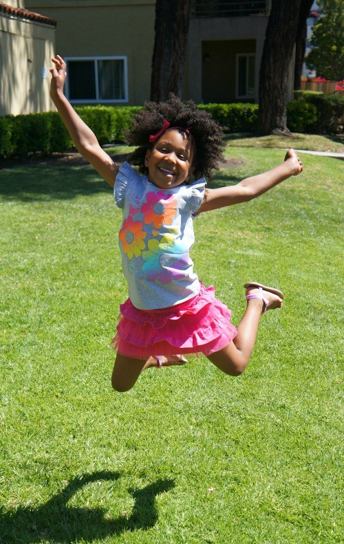 Girl jumps for joy that it's spring