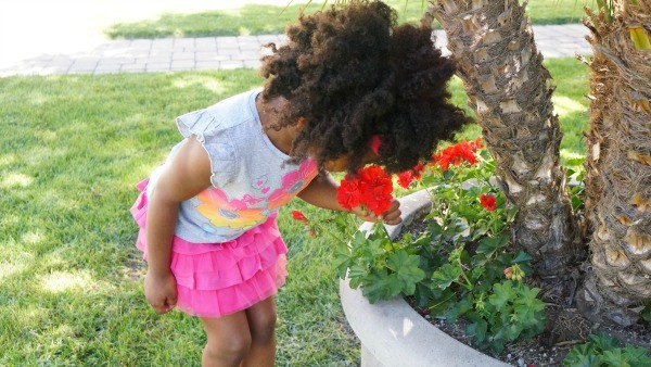 Girl smelling spring flowers in her cute Garanimals tee and skirt