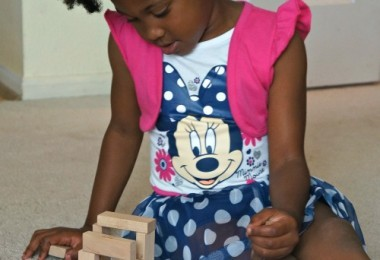 Girl building with blocks in her Disney Jr Minnie Mouse dress