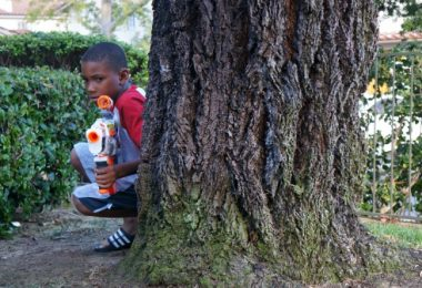 Boy hiding in backyard NERF blaster battle