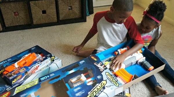 Kids open NERF blasters for a fun backyard battle!