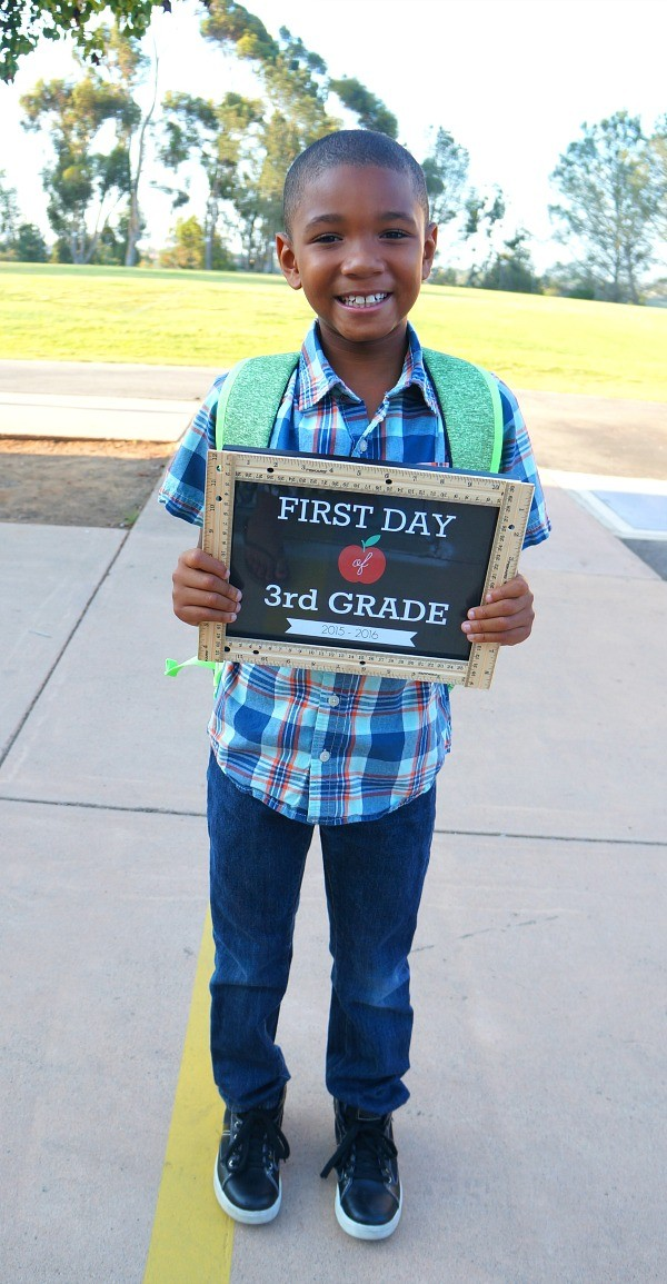 Boy holding DIY first day of school sign for 3rd grade - free printable first day of school signs