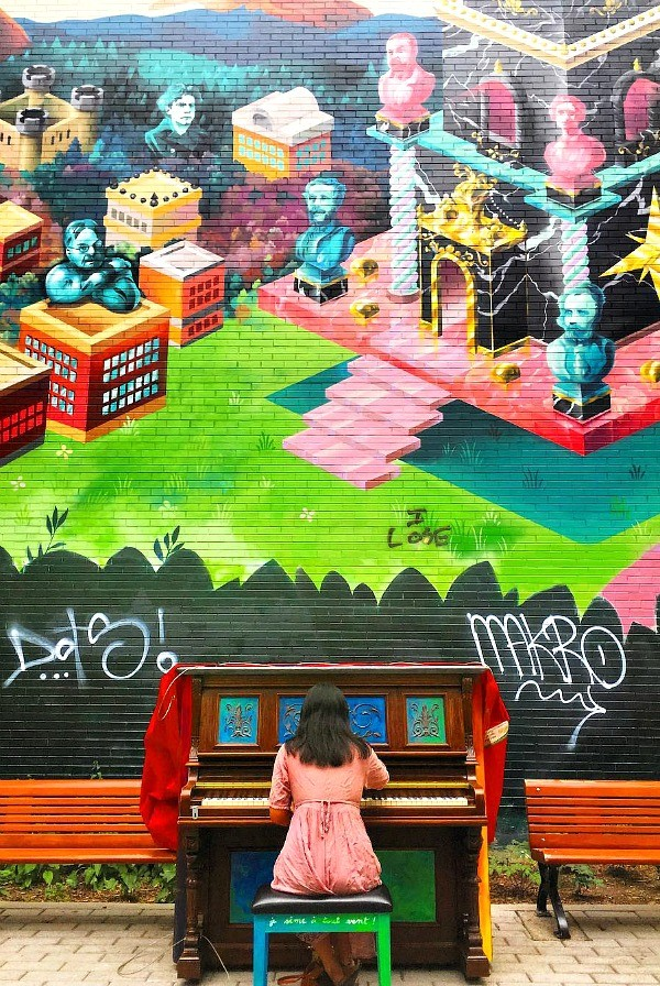 This public piano sits on a street in Montreal, Quebec, Canada on a painted wall in the summer. Locals can stop and play a tune for the whole neighborhood to hear, I love Montreal street art!
