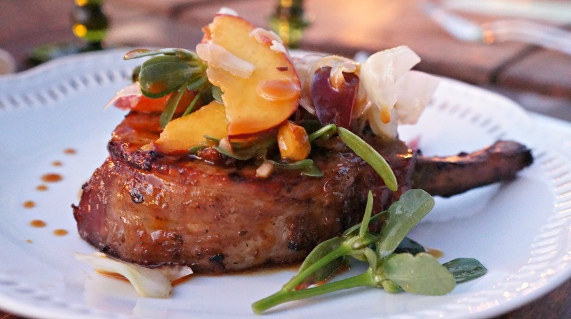 Niman Ranch pork chop made with a spicy California avocado puree, topped with a Chino farms stone fruit salad