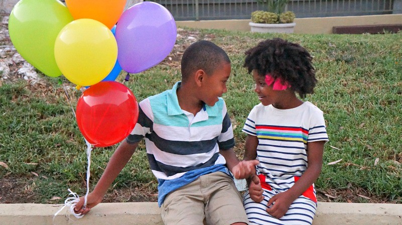 Brother and sister creative back to school photos with balloons