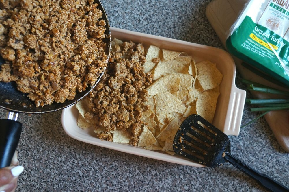 Making turkey taco casserole with tortilla chips