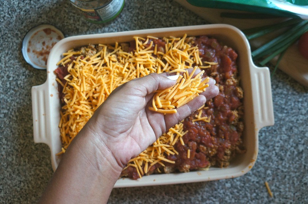 Sprinkling cheese on a turkey taco bake dinner recipe
