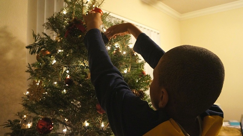 Boy decorating the Christmas tree a family holiday tradition - Copy