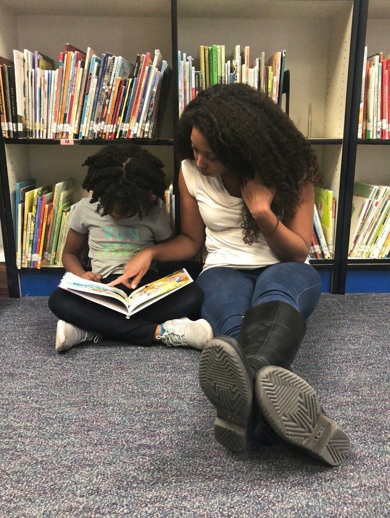 Mother and daughter reading at the library