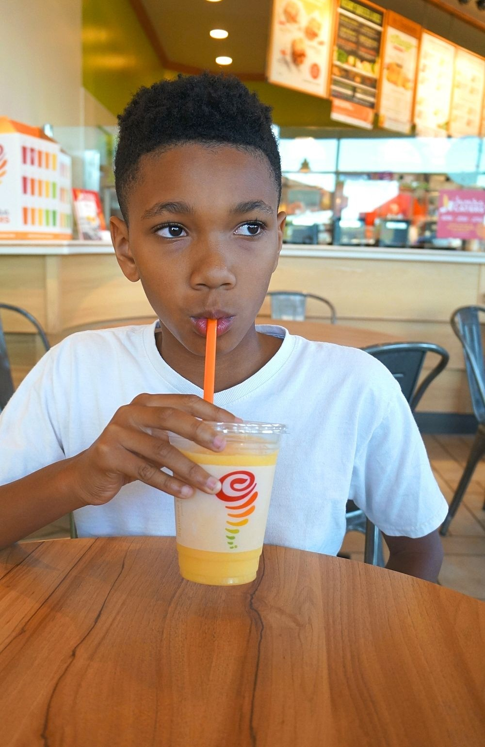 Kid drinking Mango A Go-Go smoothie at Jamba Juice