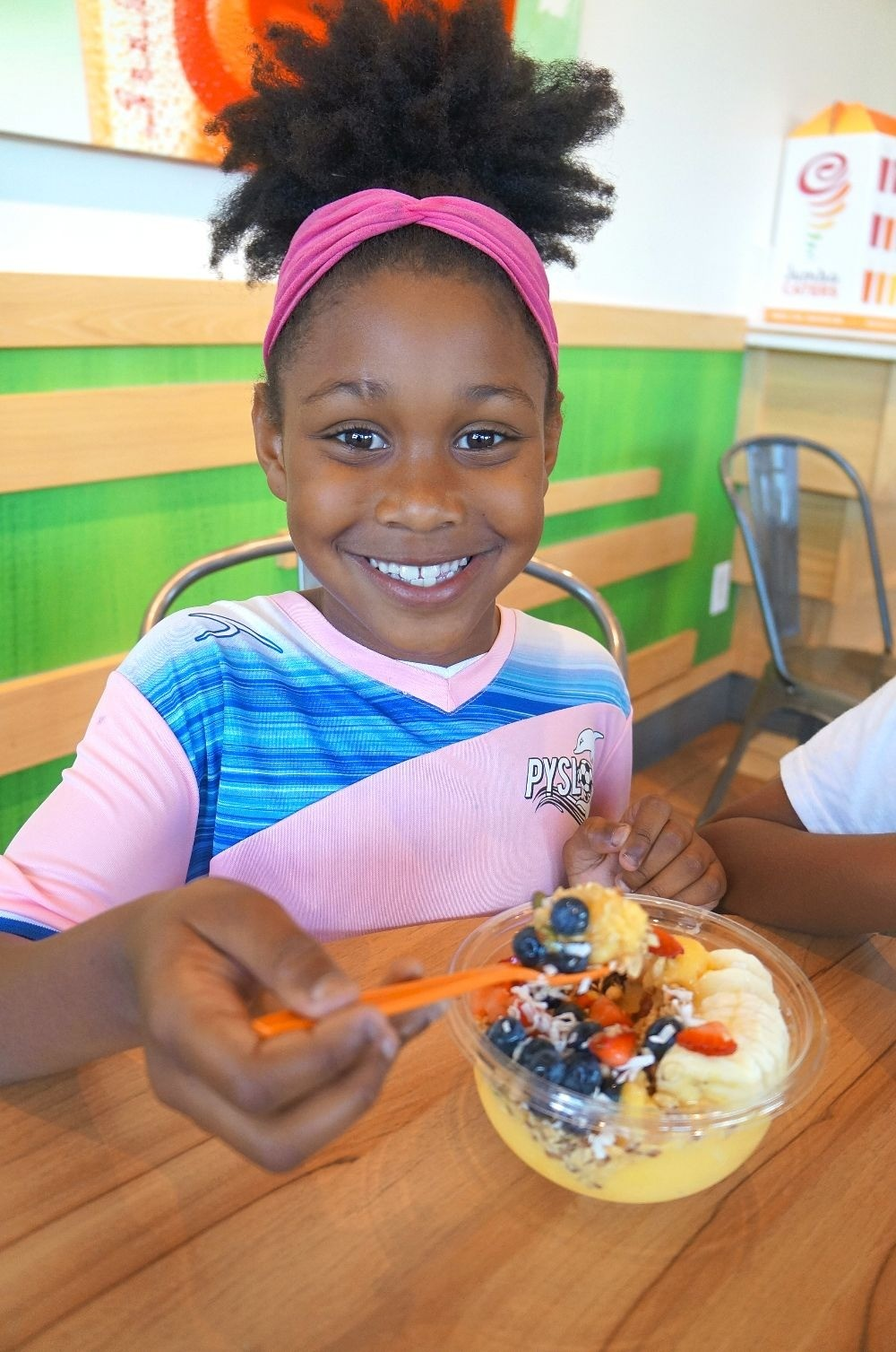Little girl eats smoothie bowl at Jamba Juice, a nutritious after soccer practice snack!