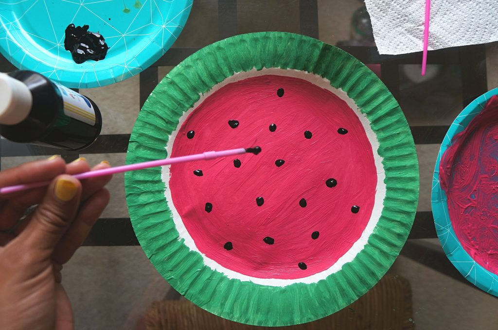 Adding black paint seeds to watermelon paper plate craft